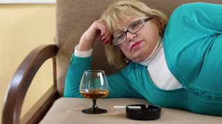 Obese depressed senior woman lying on a sofa and drinking brandy