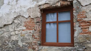 Old building with new window with venetian blind. Dilapidated brick wall of house