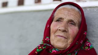Old woman looks at the camera. Elderly woman in red headscarf sits near grey wall of his house and looks at the camera. Female looks at the camera and smiles, wrinkled face