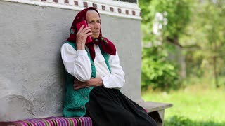 Old woman sits near grey wall of his house and talks on cell phone. Ukrainian old woman with smartphone. Old woman sits on bench near his house and speaks on smartphone. Female with smartphone