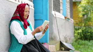 Old woman sits on bench and communicates via tablet computer. Senior woman sits on bench near his house and speaks via tablet pc in skype. Ukrainian old woman with tablet pc communicates through skype