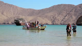 OMAN, MUSANDAM PENINSULA, GULF OF OMAN, FEBRUARY 2, 2016: People come out of boat to the shore of Musandam peninsula, Oman. Sultanate of Oman - arab country in southeastern coast of Arabian Peninsula