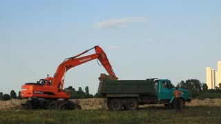 Open sandpit, excavator and green dump truck