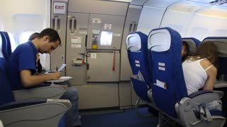 People aboard an airplane. Seating near emergency exit