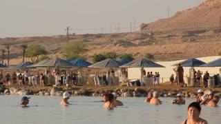 People bathe in Dead Sea in the morning, Israel. Health resort on Dead Sea in Israel