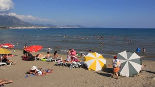 People bathing and sunbathing on the beach in Alanya, Turkey