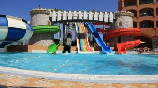 People in big many-coloured recreation area with aquapark