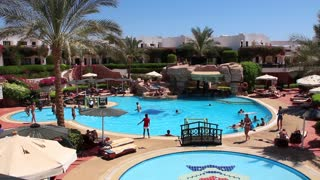 People in hotel area with swimming pool in Sharm El Sheikh, Egypt