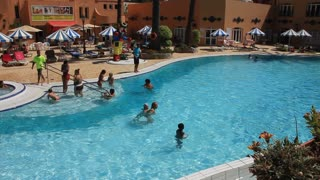 People in recreation area with blue pool