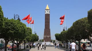 People on avenue by tower clock in Tunis, Tunisia