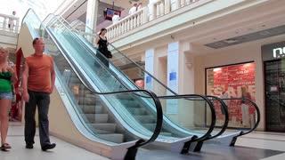 People on escalator inside shopping center