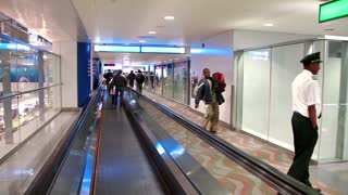 People on travelator in Dubai International Airport - the largest airport of the UAE.The maximum throughput of airport is 100 million passengers in year.