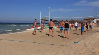 People play volleyball on a beach