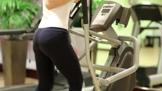 Physical activity helps burn up calories. Woman trains in gym. Woman on a orbitrek exercise equipment. The woman goes in for sports