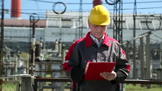 Power engineering specialist at heat station. Man writes in a worksheet. Engineering supervision at heat electric power station