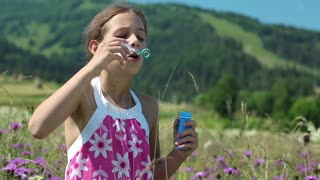 Pretty girl blowing soap bubbles on the meadow