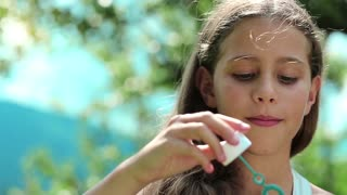 Pretty girl blowing soap bubbles