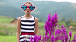 Pretty girl in big glasses in the shape of hearts looks at the camera and dance. Funny girl in big blue and red glasses on the nature. Cheerful girl jumping and hamming