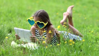 Pretty girl in big sunglasses with white tablet computer lies on green grass. Little girl in glasses lies on the green grass and uses tablet computer. Girl playing the game on his tablet computer