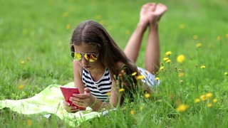 Pretty girl in sunglasses with red smartphone lies on the grass. Pretty girl playing the game on his smartphone. Little girl in glasses lies on the green grass and uses cell phone