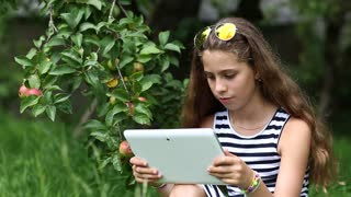 Pretty girl in sunglasses with tablet pc stands under apple tree in garden. Female in glasses with tablet pc. Girl communicates through skype. Nice girl stands under apple tree and talks via tablet pc