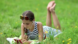Pretty girl lies on green grass and uses red smartphone. Girl type sms on his smartphone. Little girl in sun glasses lies on the grass and uses cell phone
