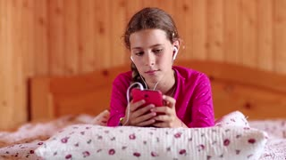 Pretty girl lies on the bed and communicates via smartphone. Female with smartphone communicates through skype. Beautiful girl lies on the bed and uses his smartphone. Girl lies on the sofa