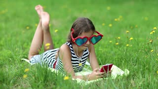 Pretty girl playing the game on his smartphone. Attractive girl in big sunglasses in the shape of hearts with red smartphone lies on the grass. Girl in glasses lies on green grass and uses cell phone