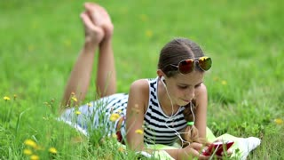 Pretty girl playing the game on his smartphone. Little girl in glasses lies on the green grass and uses cell phone. Attractive girl in sunglasses with red smartphone lies on the grass