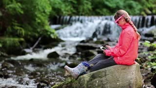 Pretty girl playing the game on tablet computer. Girl in glasses in shape of hearts with tablet pc sits near small river. Girl in red jacket with white tablet pc sits on big stone near river in forest