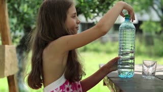 Pretty girl pours water from a bottle into a glass
