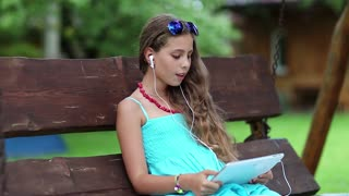 Pretty girl sits on swing bench and communicates via tablet computer. Beautiful girl with tablet computer sits on swing bench in garden. Attractive girl with tablet pc communicates through skype