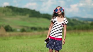 Pretty girl with red smartphone stands on the meadow, listens to music and dance. Attractive girl with smartphone listens to music and dances on green lawn
