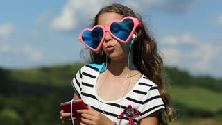 Pretty girl with smartphone stands on meadow, listens to music, dances and sings a song. Girl in big glasses in shape of hearts with smartphone listens to music, sings a song and dances on green lawn