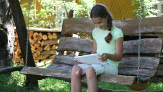 Pretty girl with tablet computer sits on the swing bench. Girl playing the game on his tablet computer. Little girl sits on the swing bench and uses tablet PC. Girl with a plait. Female with Tablet-PC