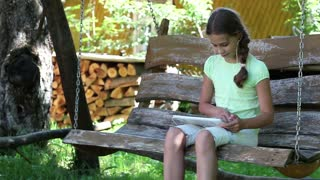 Pretty girl with tablet computer sits on the swing bench. Girl playing the game on his tablet computer. Little girl sits on the swing bench and uses tablet PC