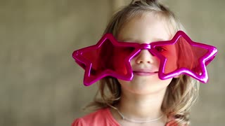 Pretty little girl in big glasses in the shape of stars looks at the camera smiles and shows his tongue. Funny little girl in pink glasses looks at the camera