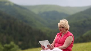 Pretty woman sitting in meadow talks on skype, gestures and smiles. She has blond hair, red T-shirt and sunglasses. Mountains behind her