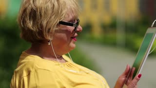 Pretty woman sitting on bench talks on skype, gestures and smiles. She has blond hair, yellow sweater and sunglasses