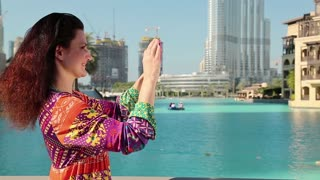 Pretty woman stands near the blue pool and makes photos on his smartphone. Female makes photos on his smartphone. Businesswoman with smartphone. Adult woman uses smartphone