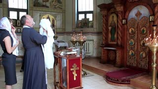 Priest with little baby in orthodox church. Infant baptism, christening