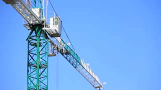 Project site. Building crane on blue background