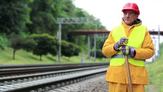 Railway man in red hard hat stands near railway track and looks at freight train. Railway worker in yellow uniform with shovel in hands stands near railway line. Workman with shovel on railway track