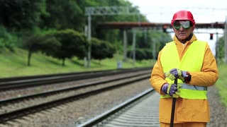 Railway worker in yellow uniform with crowbar in hands stands near railway line. Railway man in red hard hat stands near railway tracks and looks at camera. Workman with metal crowbar on railway track