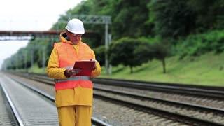 Railway worker in yellow uniform with documents. Inspector of railway traffic. Railway employee in yellow uniform on railway line. Inspector of railway traffic makes notes in his documents