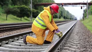 Railway worker in yellow uniform with level measuring instrument on railway line. Railway man in red hard hat sits on railway tracks and looks at the train. Workman with level measuring instrument