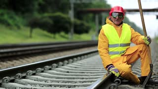 Railway worker in yellow uniform with shovel in hand sits on railway line. Railwayman in red hard hat sits on rail and looks at the camera. Workman with spade on railway track. Railway construction