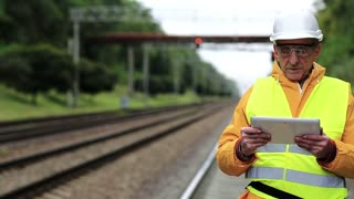 Railway worker makes notes in his tablet computer. Railway worker in yellow uniform and white hard hat with tablet pc in hands. Railway employee in yellow uniform on railway line