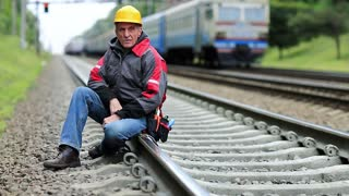 Railway worker sits on railway line. Train rides on the railroad. Railwayman in yellow hard hat sits on rail and looks at the camera. Workman on railway track