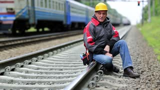 Railwayman in yellow hard hat sits on rail and looks at the camera. Workman on railway track. Railway worker sits on railway line. Train rides on the railroad